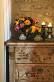 Bunch of flowers and candles on dresser