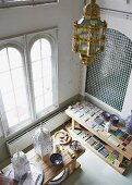 View down into ceramics workshop in industrial interior - various tile samples and Moroccan-style lanterns on wooden table