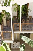Potted trees on pergola balcony of Mediterranean house and view of courtyard below