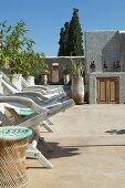 Deckchairs and potted plants on sunny, Mediterranean roof terrace