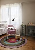 Retro standard lamp next to armchair and toys on round rug in simple child's bedroom