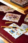 Veschiedene Papierkarten mit Schmetterlingsmotiven und goldfarbener Füller auf bordeauxfarbener Lederunterlage