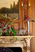 Blumenvase und Gesteck auf Kaminsims mit Schnitzereien an Holzwand mit integriertem Gemälde