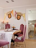Chairs with pink upholstery at dining table in corner of room with coats of arms on wall next to doorway leading to kitchen