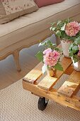Flowering potted plants on table made from pallet on castors
