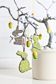 Easter arrangement with rabbits and eggs hanging from branch
