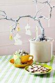 Osterbaum mit Hasen und Eiern geschmückt, darunter Tasse mit Wachteleiern und Osterplätzchen