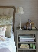 Table lamp and carafe of water on antique bedside table next to bed against grasscloth wallpaper