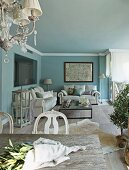 Bunch of twigs on table and white sofa set in lounge area against wall painted pale blue