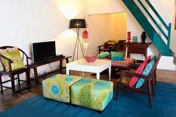 Loungeecke mit eleganten Sitzpolstern und Holzstühlen um weissen Tisch und Treppenaufgang in modernem Ambiente