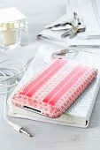iPhone decorated with red-patterned tape, earphones, notebook with white mock croc cover