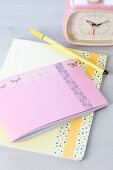 Notebook or diary decorated with tape, romantic retro alarm clock and felt-tip pen