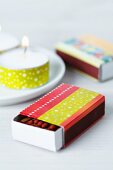 Matchbox covered in red and yellow taps and tealight decorated with yellow tape