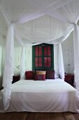 Airy, white fabric over canopied bed in front of green-painted window with closed shutters