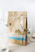A paper bag decorated with masking tape and white string between glasses and candles
