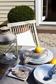Crackers next to stack of plates and lantern on garden table in front of rustic house