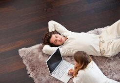 Pärchen mit Laptop auf dem Teppich