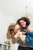 Mother playing with daughter in living-dining room