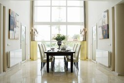 Dark wood table and chairs with white upholstery in front of floor-to-ceiling window in elegant setting