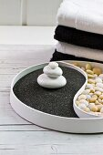 Yin and Yang dish with white pebbles on black lava sand contrasting with light pebbles