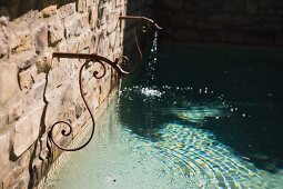 Cast iron fountain trickling into pool
