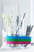 Glasgefässe als Besteckhalter mit Gummibändern verziert