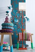 African cushions on wooden stools with knitted socks in front of floral wallpaper with some flowers cut and folded out