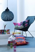 Basketwork armchair, ethnic cushions, Oriental glasses, designer pendant lamp and coffee table