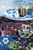 Table cloth decorated with plastic flowers and chocolate bowl with chocolate spoon on plate