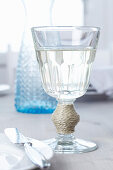 Wine glass decorated with cord wrapped around stem