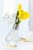 Light bulb used as vase holding freesias and gypsophila