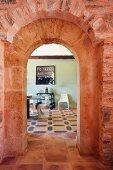 Red brick doorway between kitchen and dining room