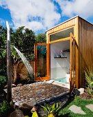 Aussendusche vor modernem Holzhaus mit offenen Türen und Blick ins Bad