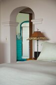 Bedside lamp next to bed and open doorway with rounded arch showing view of ensuite bathroom beyond