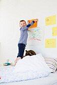 Boy hanging drawing on bedroom wall