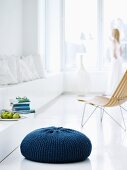 Floor cushion with hand-knitted, blue cover in minimalist, white interior