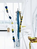 Branches covered with blue and yellow striped, knitted textiles as decoration in reserved, white interior