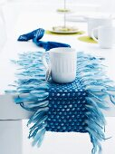 Small, woven, mottled blue table runner with long, irregular fringed edges