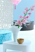 White side table with pink orchid in white vase in front of Japanese floor cushions against light blue wall