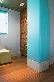 Baby blue masonry column and wood-panelled wall in window niche