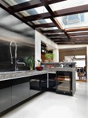 Designer kitchen counter with stainless steel splashback and stone worksurface below glass roof
