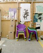 Colourful plastic nesting chairs and wooden storage boxes in front of DIY partition wall
