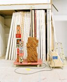 Stacked drawers next to colourful paper boxes on dolly in front of stock of wooden partition walls (furniture dolly)