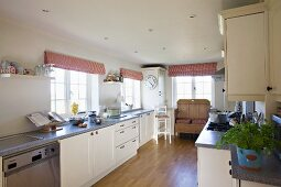 Long, modern, country-house kitchen with old wooden bench in background, red and white striped Roman blinds, parquet floor and recessed ceiling lights
