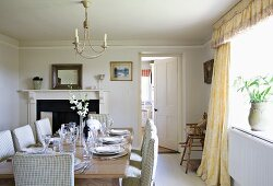 Elegant, country-house dining room in pale, Nordic shades with festively set wooden table, chairs with checked upholstery and curtains with pelmet; open fireplace and open door leading to kitchen in background.