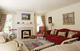 Traditional furniture with upholstery in different plain colours in bright interior with fireplace and landscape painting; gathered curtains and rug in centre of room.