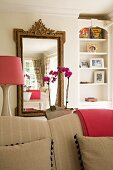 Mirror with antique-style gilt frame behind beige sofa; lampshade and folded blanket in a rich pink; feminine atmosphere in living area