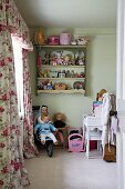 View through open door of nostalgic child's bedroom with dolls in buggy, toys on wall-mounted shelves and rose-patterned curtains with pelmet