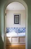 View through open arched doorway of wood-clad bathtub with tiled splashback in shades of pale blue and framed picture on wall