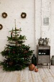 Christmas tree with lit candles next to small vintage cabinet against white wall in rustic atmosphere